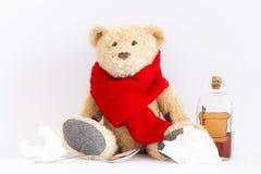 Zieke teddybeer met uitstekende geneeskundefles op witte achtergrond stock foto