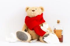 Zieke teddybeer met uitstekende geneeskundefles op witte achtergrond stock afbeelding