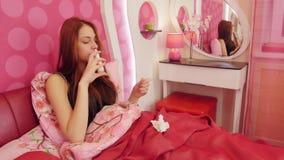 Zieke vrouw die in bed liggen en neusnevel gebruiken stock video