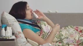 Zieke vrouw die in bed thuis liggen, nevel in neus stock footage