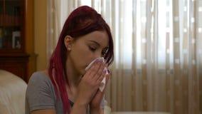 Zieke vrouw die en haar neus blazen die thuis omdat de griep blijven hoesten stock videobeelden