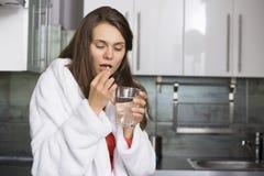 Zieke vrouw die geneeskunde in keuken nemen Royalty-vrije Stock Afbeelding