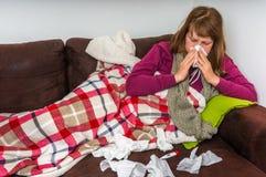 Zieke vrouw die griep hebben en haar lopende neus blazen royalty-vrije stock foto's