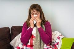 Zieke vrouw die griep hebben en haar lopende neus blazen stock afbeeldingen