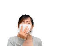 Zieke vrouw die haar geïsoleerde neus blazen Stock Afbeeldingen
