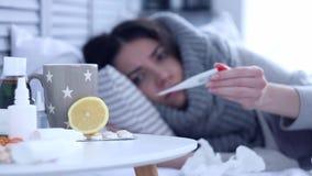 Zieke vrouw die op bed met griep bij grijze slaapkamer liggen stock footage