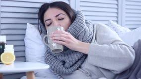 Zieke vrouw die op bed met griep bij grijze slaapkamer liggen stock videobeelden