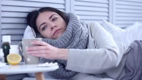Zieke vrouw die op bed met griep bij grijze slaapkamer liggen stock video