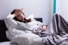Zieke Vrouw die op de Thermometer van de Bedholding liggen royalty-vrije stock foto