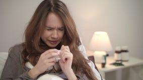 Zieke vrouw die in weefsel in bed bij avond niezen Zieke meisjes blazende neus stock videobeelden
