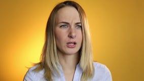 Zieke vrouw die zijn neus blazen in weefsel op een gele achtergrond stock footage