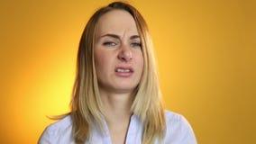Zieke vrouw die zijn neus blazen in weefsel op een gele achtergrond stock videobeelden