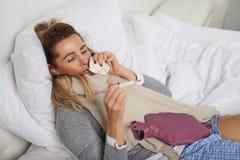 Zieke vrouw met een miserabele uitdrukking die haar temperatuur vergen Stock Afbeelding