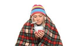 Zieke vrouw omvat met deken die een theekop houdt Royalty-vrije Stock Afbeelding