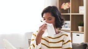 Zieke vrouwen blazende neus in papieren zakdoekje thuis stock footage