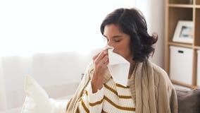 Zieke vrouwen blazende neus in papieren zakdoekje thuis stock video