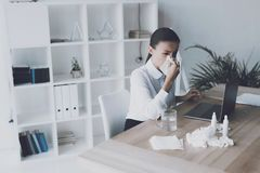 Zieke vrouwenzitting bij haar werkplaats in het bureau Een vrouw blaast haar neus in de werkplaats stock foto