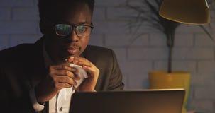 Zieke zakenman die met laptop werken en zijn neus in papieren zakdoekje blazen op nachtkantoor Zaken, werkverslaafde stock footage