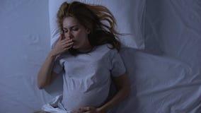 Zieke zwangere vrouw die aan misselijkheid het liggen bed, toxicosesymptoom, gezondheid lijden stock videobeelden