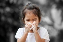 Zieken weinig Aziatisch meisjes afvegende of schoonmakende neus met weefsel royalty-vrije stock foto's