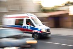 Ziekenwagen in motie het drijven onderaan de weg stock foto's