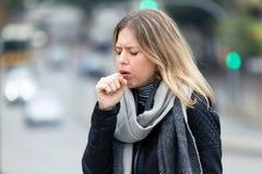 Ziekte jonge vrouw die in de straat hoesten stock afbeeldingen