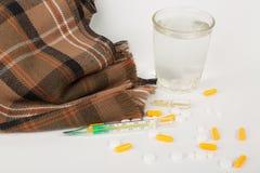 Ziekteconcept Thermometer met geneesmiddelen, glas water en deken op wit Stock Afbeeldingen