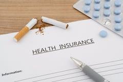 Ziektekostenverzekeringdocument met pillen en gebroken sigaret Royalty-vrije Stock Afbeeldingen