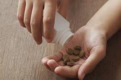zielarska medycyna w ręce na drewnie Obrazy Stock