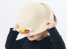 Zieleń przyglądająca się mała dziewczynka jest ubranym kapelusz na fotografia royalty free