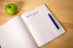 Ziele der Draufsicht 2017 listen mit Notizbuch, grüner Apfel auf dem hölzernen Desktop auf Stockfotografie