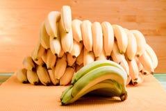 Zieleni banany i mnóstwo żółci banany na zielenieją deskę dalej Zdjęcia Royalty Free