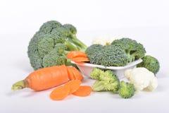 Zieleni brokuły i marchewka cią w piecies kłama na białym tle fotografia stock