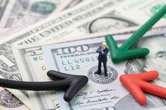 Zieleni, czerwonej i czarnej strzała wskazuje biznesmen pozycja na USA Federal Reserve emblemacie na sto dolarach banknotu KARMIĄ zdjęcia stock