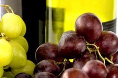 Zieleni i czarni winogrona z dwa wino butelkami Zdjęcia Stock