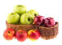 Zieleni i czerwoni jabłka w łozinowi kosze obraz stock