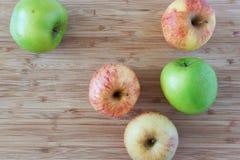Zieleni i różowi jabłka na drewnianym tle Zdjęcie Stock