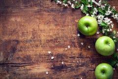 Zieleni jabłka i czereśniowi okwitnięcia na drewnianym tle Zdjęcia Royalty Free