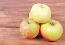 Zieleni jabłka kłama na drewnianym tle Obrazy Stock