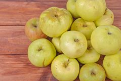 Zieleni jabłka kłama na drewnianym tle Fotografia Royalty Free