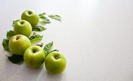 Zieleni jabłka na białym stole Fotografia Stock