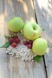 Zieleni jabłka obok malinki z liśćmi agresty i wiązką oatmeal Zdjęcia Stock