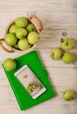 Zieleni jabłka w koszu, zielony notatnik i biel, dzwonią na li Obrazy Royalty Free