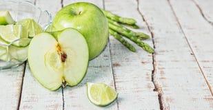 Zieleni jabłka, wapno i szparagowego Ð ¾ n biały drewniany stół, Obraz Stock