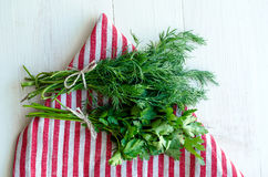 Zieleni pietruszki i koperu liście na naturalnej bieliźnianej pielusze na drewnianym tle Fotografia Stock