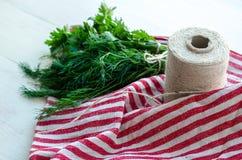 Zieleni pietruszki i koperu liście na naturalnej bieliźnianej pielusze na drewnianym tle Obrazy Royalty Free