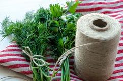 Zieleni pietruszki i koperu liście na naturalnej bieliźnianej pielusze na drewnianym tle Zdjęcia Stock