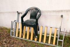 Zieleni plastikowi ogrodowi krzesła rzucający daleko od i opuszczali na drabinie ścianą w ogródzie 3d tło odpłaca się tekstury śc Obraz Stock
