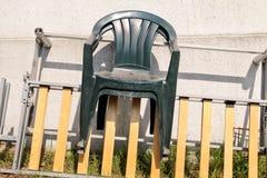 Zieleni plastikowi ogrodowi krzesła rzucający daleko od i opuszczali na drabinie ścianą w ogródzie 3d tło odpłaca się tekstury śc Fotografia Stock