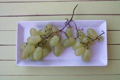 Zieleni winogrona w białej tacy na zielonym drewnie od above Zdjęcie Stock